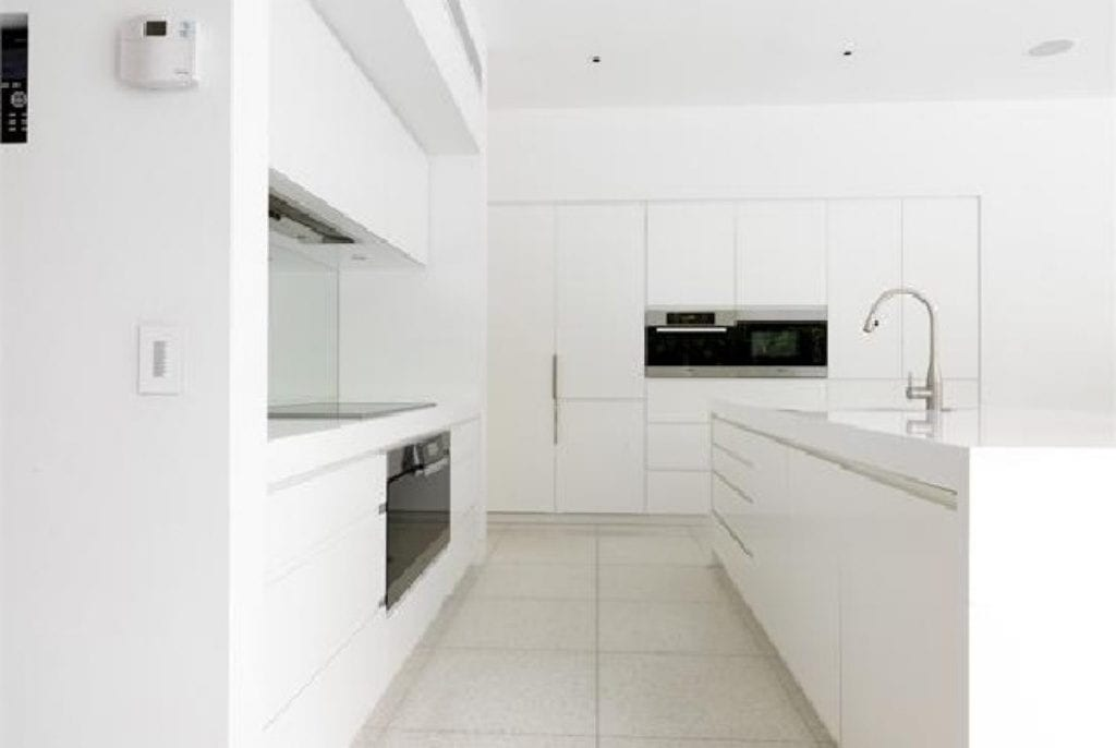 Crisp white kitchen with large edges & waterfall ends